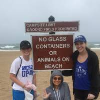 3 female students pose with a sign at Grand Haven Beach